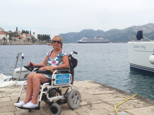 Customer smiling for the camera while using a powerchair, with cruise ship in background.