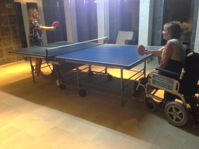 Customer using our powerchair while playing table-tennis on board cruise ship.